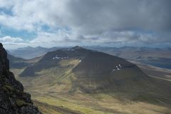 Toneelmening aan het landschap met geërodeerde bergen in groen op de Faeröer stock fotografie