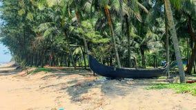 Toneelmening aan tropisch strand met traditionele vissersboot en strandhutten op de kokospalmenachtergrond in Kerala, Zuiden stock afbeeldingen