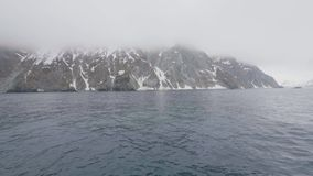 Toneelmening over bergen met sneeuwpieken en rotsachtige klip in oceaanwater stock video
