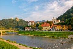 Toneelmening over rivier Savinja, Capuchin klooster, huizen in Breg en kasteelheuvel in Celje, Slovenië stock foto's
