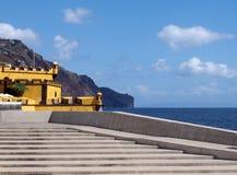 toneelmening van concrete stappen op de strandboulevard in Funchal met een mening van de oceaanklippen en het gele fort van Saoti royalty-vrije stock foto