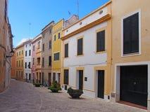 Toneelmening van een lege straat van heldere geschilderde gele traditionele huizen in ciutadellamenorca met heldere blauwe de zom stock afbeeldingen