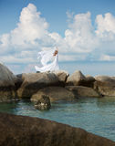 Toneelmening van een vrouw in witte kleding die zich op de rotsen bevinden Stock Foto