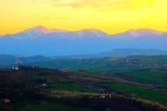 Toneelmening van hierboven bij heuvels en bergen onder de gele zonsonderganghemel stock afbeelding