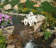 Toneelmening van kleurrijke bloembedden en windend gazongras in een aantrekkelijke tuin Beeldhouwwerk van Engelen over de waterva royalty-vrije stock foto's