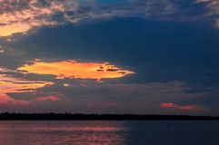 Toneelzonsondergang met oranje bewolkte hemel over een meer stock foto's