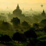 Toneelzonsopgang met silhouetballons boven ruïnepagode in Bagan, Myanmar stock afbeeldingen