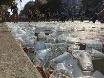 Toneladas de gente plástica vacía de las tazas que corre encima en Berlin Marathon fotografía de archivo