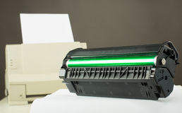 Printer toner cartridge. Toner cartridge against laser printer stock image