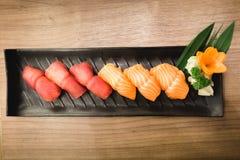 Tonfisk och Salmon Sushi på den svarta maträtten, trätabell Royaltyfri Bild