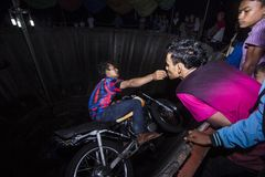 Tong Setan Show. A Stunman rider on Tong Setan show, take money from an audience lips. Tong Setan is a dare devil show where a rider without safety spin in a Royalty Free Stock Image