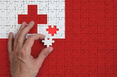 Tonga flag is depicted on a puzzle, which the man`s hand completes to fold.  vector illustration