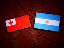 Tongan flag with Argentinian flag on a tree stump  Royalty Free Stock Photos