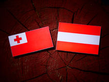 Tongan flag with Austrian flag on a tree stump  Royalty Free Stock Images