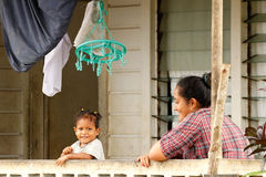 Tongan woman with a child sitting on a front porch of her house, Stock Images