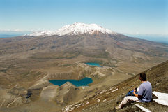 Tongariro crossing, New Zealand. Male trekker sitting on the summit of Ngauruhoe volcano, viewing Tama Lakes and Ruapehu volcano. Tongariro track, New Zealand royalty free stock image
