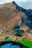 Wild rocky landscape with Emerald blue lakes under the high mountain peak in World`s Heritage Tongariro National Park royalty free stock image