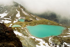 Tongariro lakes with snow, New Zealand. The Emerald Lakes of the Tongariro during winter time with snow patches and fog, Tongariro National Park, New Zealand stock images