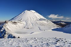 Mount Doom in the snow, winter landscape in Tongariro national park. Tongariro national park in winter weather. Sunny winter day, snow and ice covers the peak of stock photos