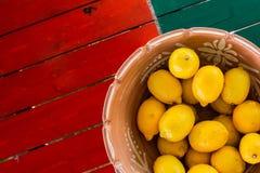 Tongefäßkorb von Zitronen auf der coloful Tabelle mit copyspace stockfoto