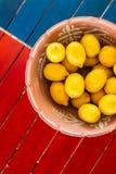 Tongefäßkorb von Zitronen auf der coloful Tabelle mit copyspace lizenzfreie stockfotografie