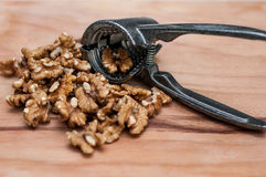 Tongs for chopping walnuts and shelled walnut Royalty Free Stock Photography