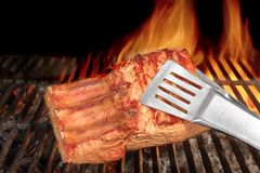 Tongs Holding Grilled Pork Ribs. Hot Flaming BBQ Grill on the Background Stock Photography