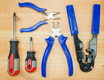A tongs, pliers, Crimping pliers and two screwdriv. Ers on a wooden board Royalty Free Stock Images