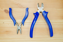 A tongs and pliers tools on a wooden board. A tongs and pliers tools on wood stock image