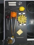Aesthetics assorted kitchen utensils on a black kitchen counter. Tongs, potato slicer, cheese, can opener Stock Photo