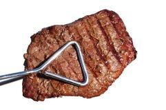 Tongs que prendem o bife grelhado do Sirloin da parte superior do lombo de carne Fotos de Stock Royalty Free