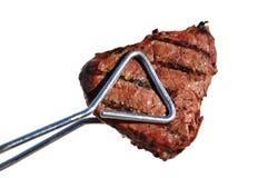 Tongs que prendem o bife grelhado do Sirloin da parte superior do lombo de carne Foto de Stock