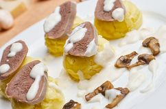 Tongue dish with horseradish sauce. Boiled beef tongue with Hominy white sauce with mushrooms Royalty Free Stock Image