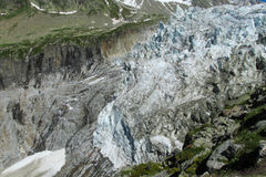 The tongue of the glacier descends to alpine valley. The tongue of the glacier descends into the valley of the Alps royalty free stock photo