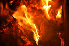 Tongues of flame on the burning coals. Royalty Free Stock Images