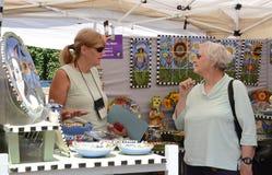 Toni Mann at Ann Arbor Art Fair. ANN ARBOR, MI - JULY 20: Toni Mann, a ceramics artist from Lake Worth, Florida, speaks to a customer at the Ann Arbor's South Royalty Free Stock Photos