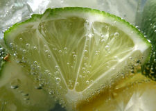 Tonic bubbles on lime. Through the glass Stock Images