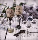 Tonificado perto acima de garrafas bonitos com etiquetas coma-me e beba-o me, a chave, as bolas de cristal e as flores Imagem de Stock