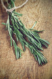 Toning effect sprigs of rosemary on a wooden board closeup horiz. Ontal low angle view Royalty Free Stock Images