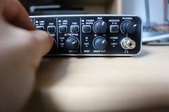 Toningenieur reguliert Volumen auf Audioschnittstelle in einem Tonstudio Stockbilder