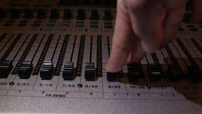 Toningenieur senkt die Schieber der Tonspuren auf dem Tonmeister und stellt den Ton ab stock footage