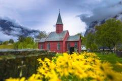 Tonjum, Noorwegen - Mei 14, 2017: Gele bloemen door de Rode kerk stock foto's