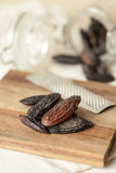 Tonka bean. S on a wooden plate and with a grater Stock Image