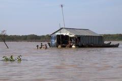 Tonle seiva Camboja 4 de janeiro de 2018, barco de casa tradicional com as crianças que jogam na água enlameada imagens de stock royalty free