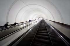 Tonnel with escalators, people in motion blur Royalty Free Stock Image