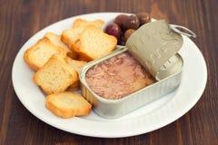 Tonno in contenitore di ferro con i pani tostati e le olive sul piatto Fotografie Stock