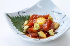 Tonno rosso tagliato Tuna Salad di Maguro con l'avocado tagliato ed il tuorlo d'uovo serviti sul piatto ceramico dipinto inchiost fotografia stock