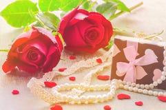 Tono caliente del color de pares de la rosa del rojo con el corazón, el ornamento de la perla y la decoración de la caja de regal Imagenes de archivo