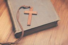 Tono d'annata della collana trasversale cristiana di legno sulla bibbia santa Immagine Stock Libera da Diritti