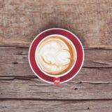 Tono d'annata della tazza di caffè rossa sulla tavola di legno Immagini Stock